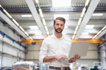 Portrait of young male engineer using laptop in engineering factory