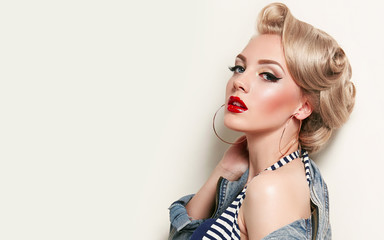 Beautiful young american girl in retro style, pinup. Blond, hairstyle - light curls. Retro make-up...