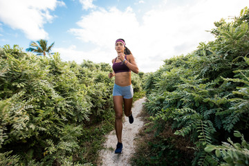 Young woman exercising outdoors, running, South Point Park, Miami Beach, Florida, USA