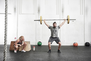 Man lifting barbell in cross training gym