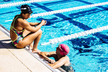 Swimmer sitting at end of pool talking to friend