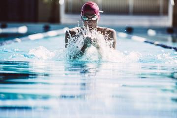 Swimmer splashing pool water on face