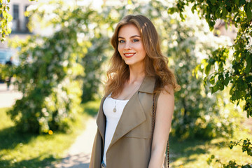 Happy beautiful woman in fashionable brand clothes posing in the park on a sunny day
