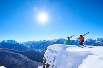 Two male skiers looking out from snow covered ridge, Aspen, Colorado, USA