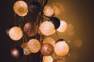 Cotton light balls shining in the dark in a home interior. Creative decoration.