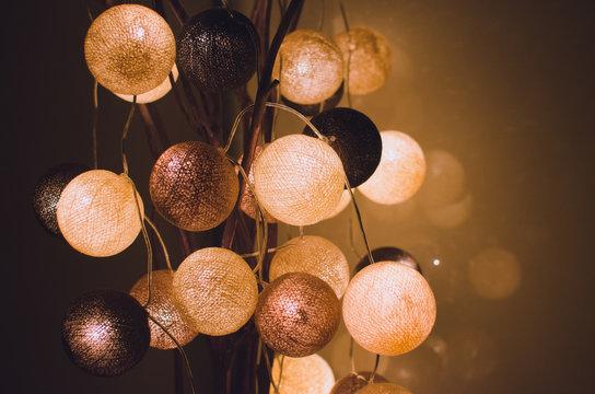 Cotton light balls shining in the dark in a home interior. Creative decoration.