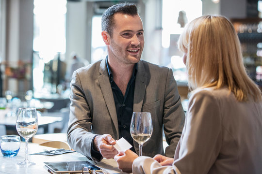 Businessman and businesswoman making introductions at lunch in restaurant