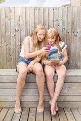 Girls sitting in garden using digital tablet and smartphone smiling