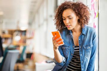 Female digital designer on office desk looking at smartphone