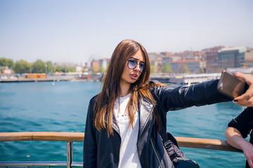 Woman taking selfie, sea in background