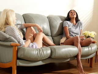 Friends sitting on sofa laughing