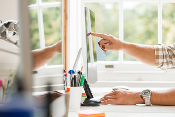 Hand of male designer pointing at desktop computer in creative studio