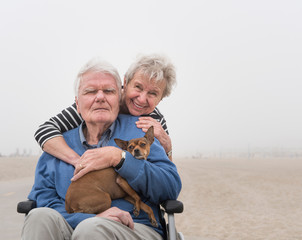 Portrait of senior man in wheelchair with wife and dog at beach, Santa Monica, California, USA