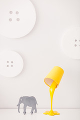 A yellow lamp in the form of a bucket of paint is on a white nightstand. Nearby is a statuette of a gray elephant. In the background, the decor in the form of huge buttons
