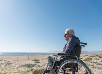 Senior man in wheelchair looking out from dunes, Playa del Ray, California, USA