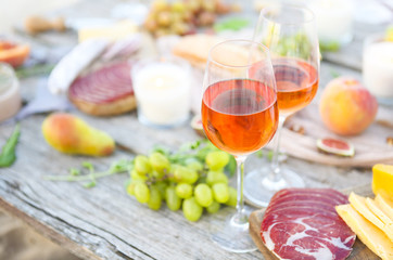 Picnic with rose wine fruits meat and cheese