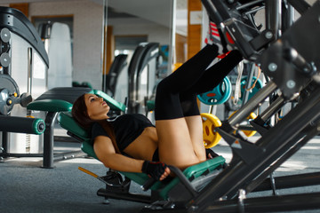 Beautiful young woman with a sexy body in black socks and a t-shirt workout in the gym