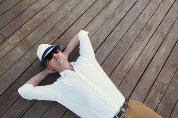Young man lying on wooden deck