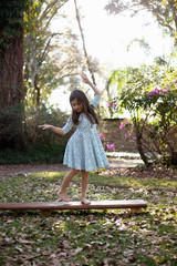 Girl balancing on wooden step in shaded garden