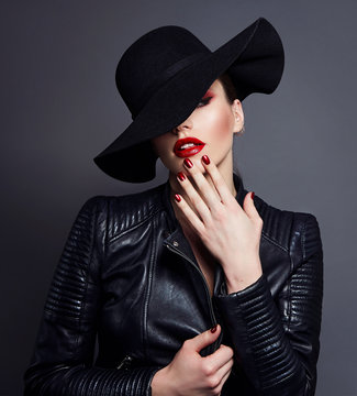 Beautiful young mysterious girl in a black hat and black leather jacket on a gray background. Eyes are covered with a hat. Makeup - red lips. Manicure - long red nails, nail polish. Fashion, beauty.