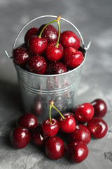 Wet sweet cherry in a small bucket on a concrete background