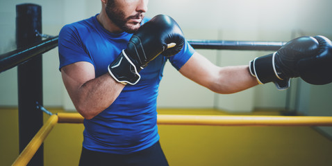 Young man boxing workout on ring in a fitness club. Caucasian male boxer in black gloves. Muscular strong man on background boxing gym.Horizontal wide.