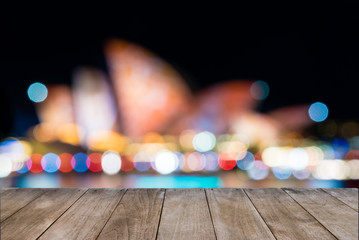Empty wooden table in front of blurred unidentifiable blurred Sydney Opera House in background