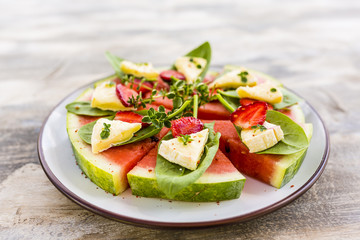 Delicious watermelon pizza with cheese and herbs on a wooden table.