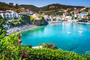 Bali, Island Crete, Greece, Sunny day scenery scenery with mountains, Mediterranean sea, flowers and pier with boats and ship for walking tourists in the sea near village Bali