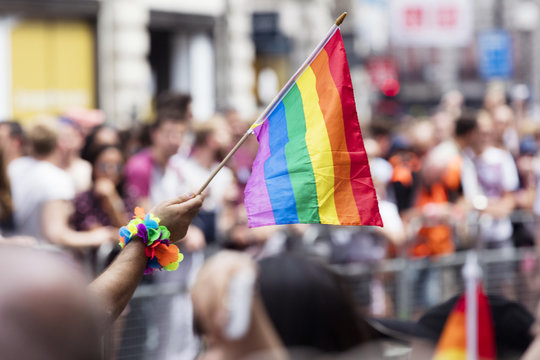 Man's hand waving rainbow flag during pride march