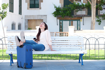 Full body woman sitting with suitcase and phone on park bench