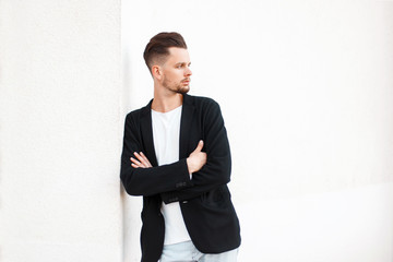 Handsome stylish man with hairstyle in business fashionable clothes near white wall