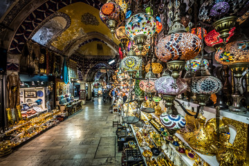 Unidentified Tourists visiting and shopping in the Grand Bazaar in Istanbul.traditional handmade decorative mosaic multi-colored Turkish lamps for sale hanging on the front side.