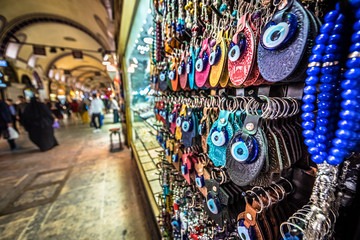 ISTANBUL, TURKEY- APRIL 17, 2017: Unidentified Tourists visiting and shopping in the Grand Bazaar in Istanbul. Interior of the Grand Bazaar with souvenirs on the foreground