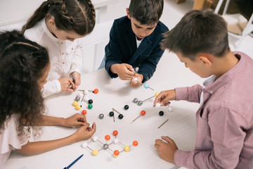 Concentrated multiethnic schoolkids studying with molecular model at chemistry lesson