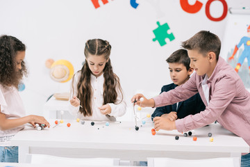 Multiethnic group of schoolchildren studying with molecular model at chemistry lesson