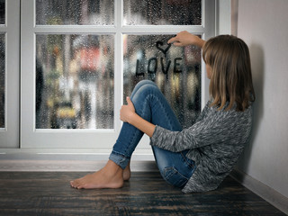 """Girl writes on the wet window text """"love"""" and draws a heart"""
