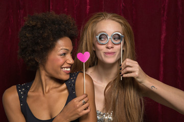 Girl friends posing at photo booth party