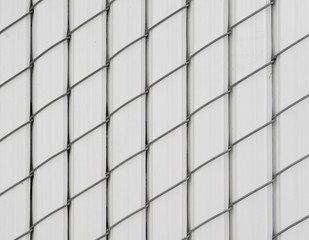 Chain-linked fence, plastic stripes woven with wire