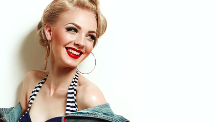 Beautiful bright girl in retro style, pin-up, smiling. Hairstyle - blonde hair, blonde, retro hairstyle. Clothes, fashion, beauty. Makeup - red lipstick, black arrows, false eyelashes.