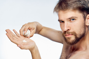 A young guy with a beard on a white isolated background applies a shaving cream