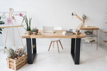 florist workplace with board, dry flowers and laptop in modern office