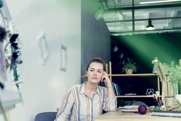 pensive attractive businesswoman sitting at table in modern office