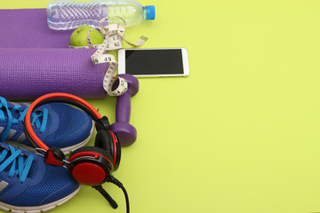 Wall Mural - Athlete's set  dumbbells and bottle of water, Yoga mat, sport shoes,  on yellow  background. Concept healthy lifestyle, sport and diet. Sport equipment. Copy space