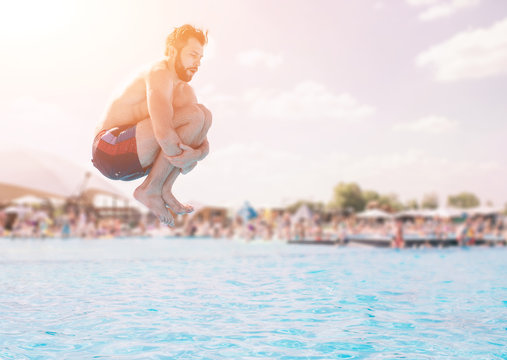 Man in blue and red shorts jumping in swimming pool at sunny day. Enjoying pool party with friends.