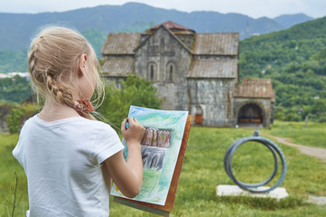 Schoolgirl drawing an ancient armenian church in monastery Akhtala