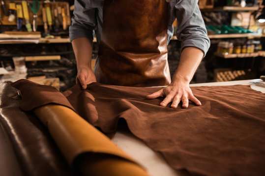 Close up of a cobbler working with leather textile