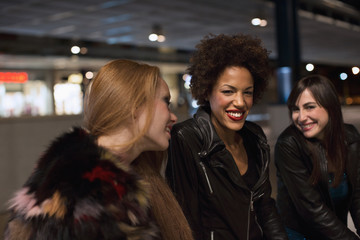 Three female friends sitting outside train station laughing before going out clubbing in the evening