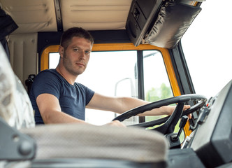 Male trucker in cabin of his yellow truck.
