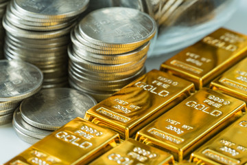 shiny gold bars with stack of coins as business or financial investment and wealth concept